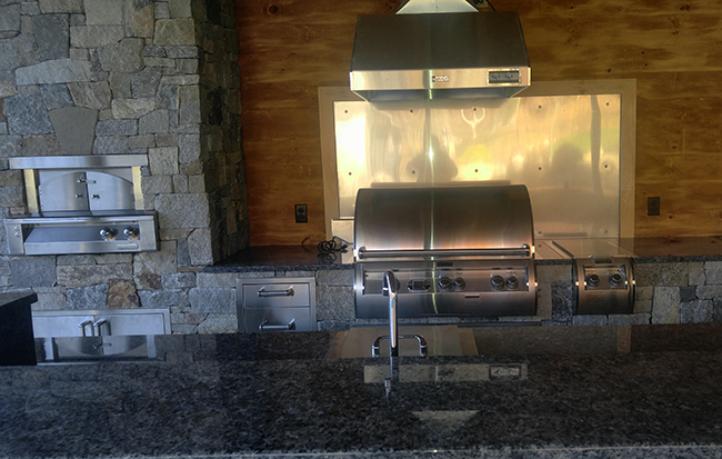 Custom stone outdoor kitchen desigin with grill, sink, and pizza oven