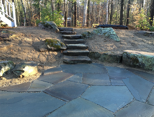 Large stone patio with rustic stairs in Dunbarton NH