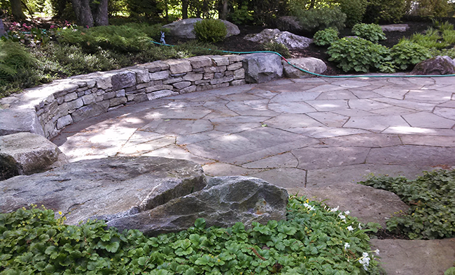 Stone patio and curved sitting wall in Dunbarton NH